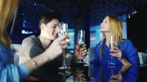 Egy elegáns fiatalember egy dátum ünnepli meg egy étteremben. Ő elfogadja, Gratulálunk, taps pohár borral