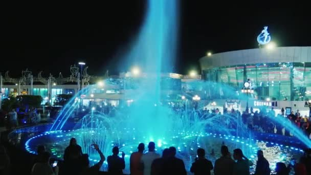 Sharm el Sheikh, Egypt, March, 2017: A glowing fountain in Soho Square. A crowd of tourists admire the beautiful spectacle, are photographed against the background of jets of colored water