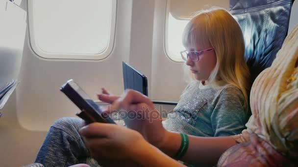 Máma a dcera létat v letadle, použijte tabletu a telefonu. Technika na silnici