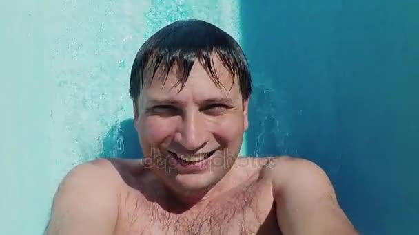 Caucasian man resting in aquapark, pulling down from water slide, looking at camera