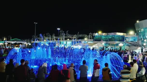 Sharm el Sheikh, Egypt, March, 2017: A crowd of tourists admiring the singing fountain in Soho Square. The torch of fire flashes above the streams of water