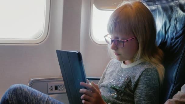 die Blondine mit der rosafarbenen Brille das Mädchen von 6 Jahren fliegt im Flugzeug, benutzt ein Tablet.