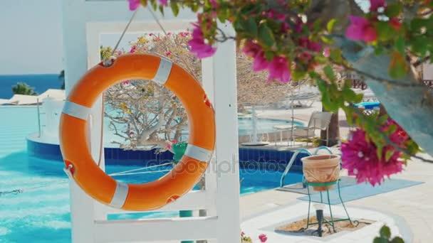 Rettungsring am Pool. Im Vordergrund blüht der Busch, von hinten sieht man das Meer und den Pool. Sichere Erholung in einem Luxushotel