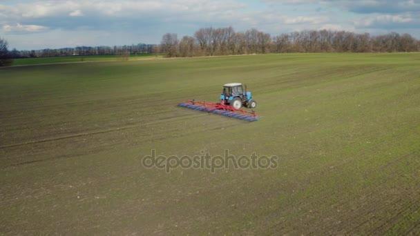Letecký pohled na traktoru, funguje pole brzy na jaře za slunečného dne. První výhonky pšenice jsou viditelné, modrá obloha s mraky