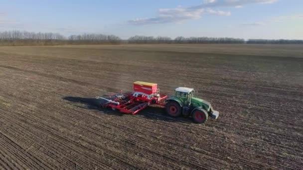 Přes pole táhne traktor velké secí stroj. Výsev kampaň v brzy na jaře, venkovské krajiny. Boční pohled. Koncept - moderní agropodnikání