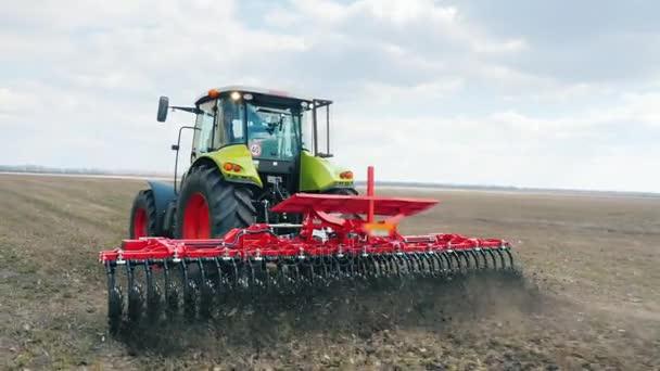 Zemědělské práce v oblasti brzy na jaře. Traktor rychle opustí dopředu na hřišti, otřesný půdy