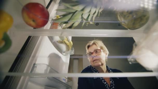 Starší žena načte produkty v ledničce. Přinesl domů nákup - mléko a džus. Čerstvé potraviny, zdravé stravování
