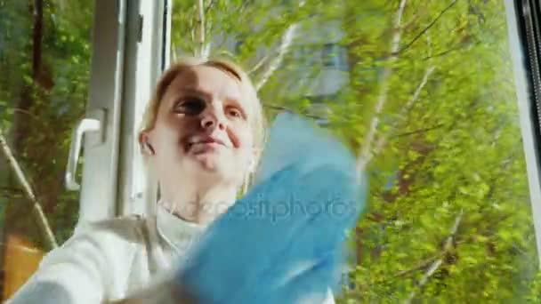 junge Frau hört Musik über Kopfhörer und läuft zu Hause - wäscht Fenster. Frühjahrsputz in der Wohnung