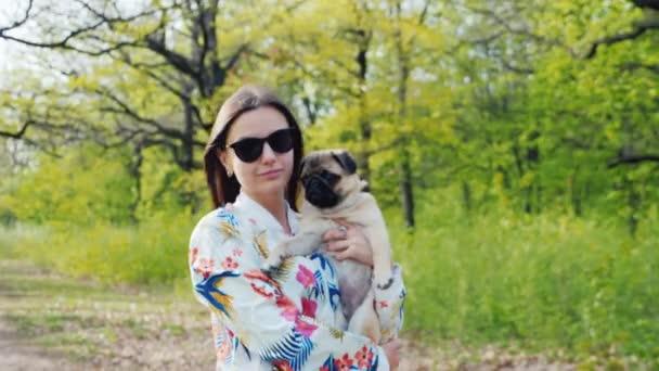 Séta a parkban-val-a kedvenc mopsz kiskutya. Fiatal nő hordozza a potot a cookie-k, sétál a tavaszi erdő