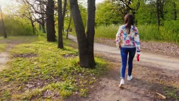 Mladá žena se slunečními brýlemi, procházky se psem v parku. Jde proti pozadí malebnou přírodou podél cesty. Zadní pohled