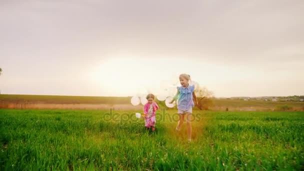 Dvě bezstarostné holčičky s balonky. Bavte se běží přes zelené louce při západu slunce. Šťastné dětství, sen o dítě. Zpomalené video