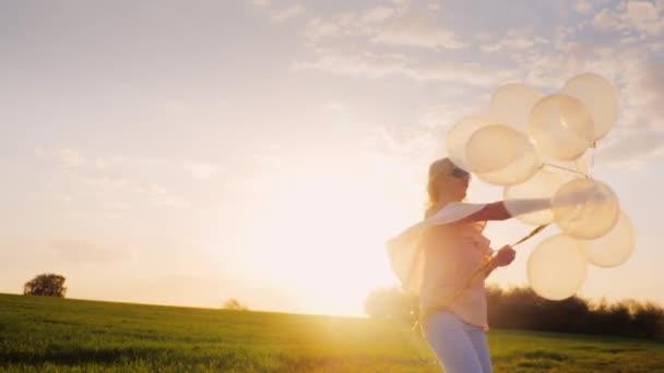 Bezstarostné mladá žena s balónky procházky při západu slunce na zelené louce. Koncept - lehkost a svobodu pohybu, snít. 4k video