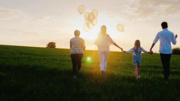 Pro několik generací rodiny chodí podél zelené louce směrem k západu slunce. Koncept - rodinné hodnoty, komunikace, šťastné dětství. Pohled zezadu