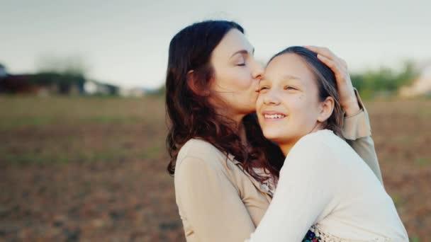 Mama jemně obejme svou dceru 11 let. Společně vypadají jedním směrem k zapadajícímu slunci. Rodinné hodnoty