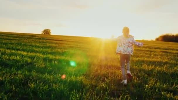 A carefree child runs happily through the green meadow. The girl enjoys a beautiful day and a beautiful sunset