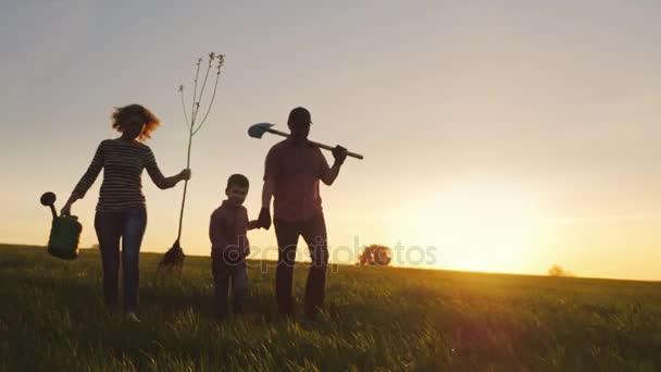 Přátelská rodina se mladý syn bude zasadit strom. Nést semenáč, lopatu a konev. Siluety v krásné oblasti na západ slunce pozadí