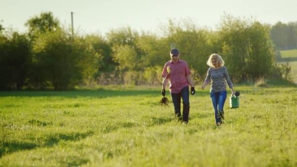 Mladý pár farmářů chůze po venkovské silnici poblíž zeleného pole. Nést Sazenice stromů a konev. Výsadba stromů, práce na venkově