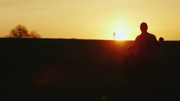 Father and son planted a tree. The man is hugging the boy, they are looking forward together to the horizon. Silhouette photography at sunset. Copyspace composition