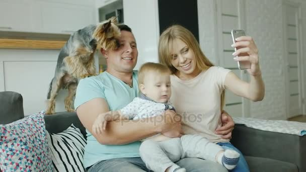 A young family - father, mother, little son and a dog do selfie at home. They sit on the couch, smile at the camera, take pictures with the phone. Happy family