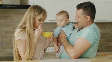 Dad and mother feed their little son together. A man holds a child on his chickens, his mother feeds him from a spoon. Baby food, happy family