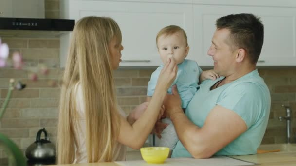 Young parents play with their little son, they try to feed him from a spoon
