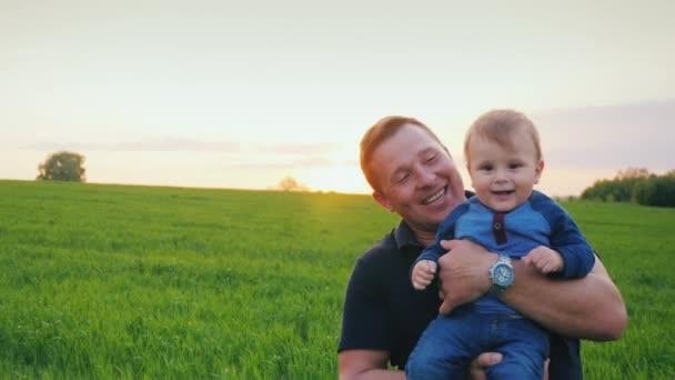 Egy fiatal, boldog apa tart egy éves fia a karját. Festői helyen, a naplemente. Slow motion videót