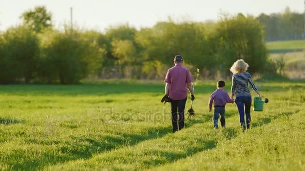 A couple of farmers are walking along a picturesque rural road. With them their little son. Go to plant a tree, carry a shovel and watering pad. Back view