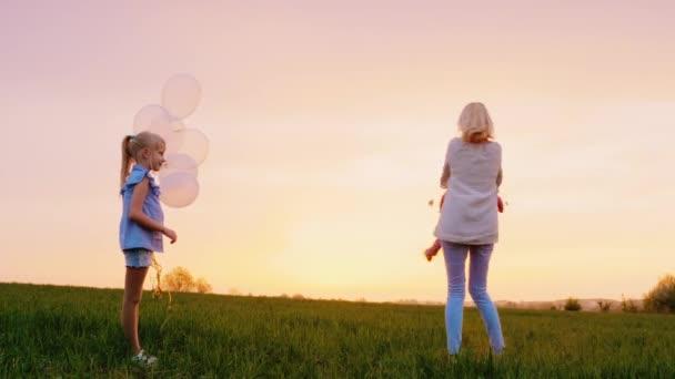 Šťastná matka dvou dívek, hraje si s nimi při západu slunce. Jeden se změní na rukou, druhá dcera se dívá na ni