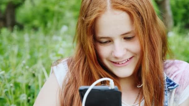 Usměvavý zrzavý dospívající dívka se těší smartphone v přírodě. Portrét na pozadí zelených stromů v parku