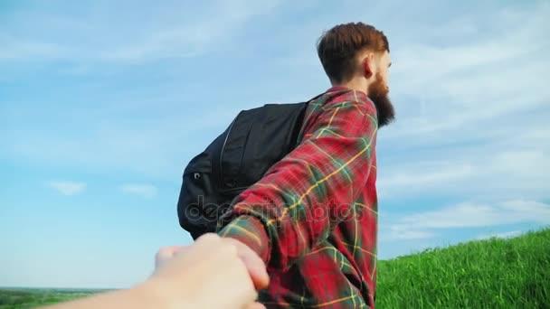 Pomocnou ruku. Mladý muž pomáhá partnera vylézt na horu. Vytáhne ji za ruku. Koncept - pomoc, podporu, spolehlivého partnera, týmová práce