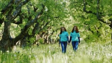 Sisters-twins together walk in the apple orchard