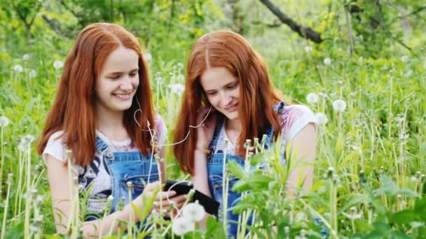 Two cool twins girls are listening to music outdoors. Beautiful red hair, smiling, having a good time. 4K slow motion video