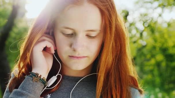 Porträt eines hübschen rothaarigen Teenagers. Sie genießt Musik von der untergehenden Sonne