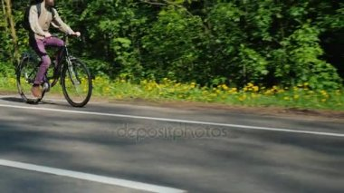 Tilt steadicam shot: A cyclist appears in the empty frame. He goes on a bike ride against the background of a green forest. Good spring day