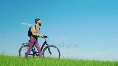 A young hipster man drives a bicycle through a green meadow. Beautiful scenery, picturesque place.