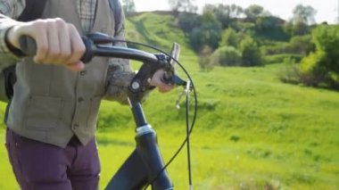 A man drives a bicycle through a green meadow. In the frame you can see his hands and the rudder of a bicycle