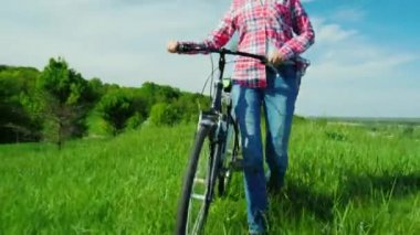A young woman drives a bicycle through a green meadow. Idialistic landscape, beautiful spring colors