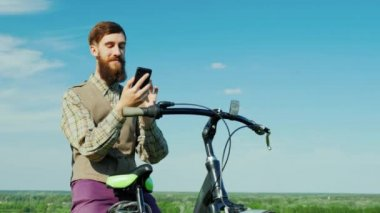 Portrait of A young man sits on a bicycle in a picturesque place. Uses a mobile phone. 4K video