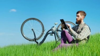 A young bearded man uses a tablet. Sits on a green meadow near his bicycle