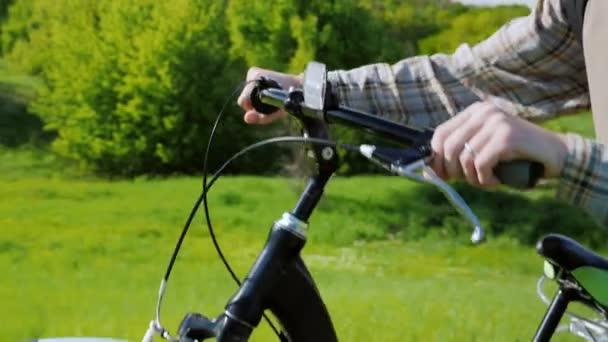 Ruce muže jezdit na kole za volantem. Na pozadí zelenou louku za slunečného dne. Ectotourism, zdravé a aktivní způsob života