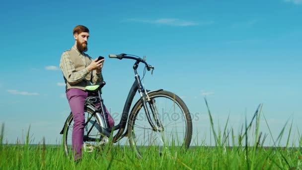 Mladý muž sedí na kole na malebném místě. Využívá mobilní telefon. 4k video