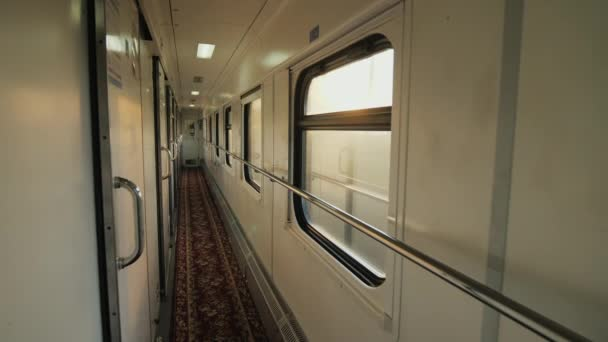 Inside the passenger railway car. The train rides fast, the morning sun shines through the windows