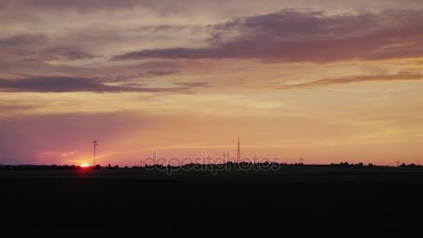 Kotouč zapadajícího slunce nad polem v krajině. Pohled z okna jedoucího auta