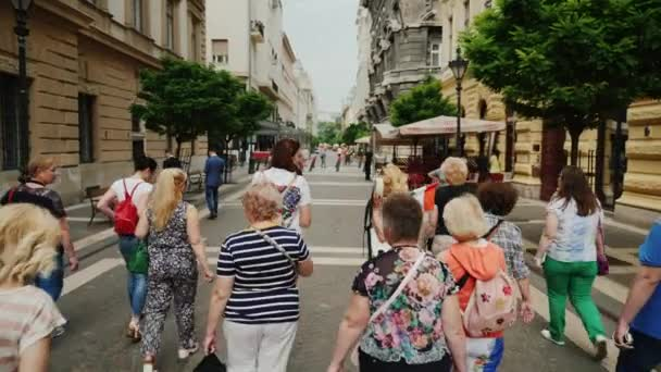 Budapest, Hungary, June 2017: A group of tourists with a guide walking the narrow streets of Budapest. Tourism in Europe