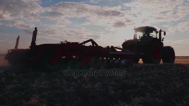 Steadicam výstřel: traktor brány pole při západu slunce.