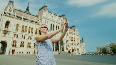 A female tourist photographs herself against the background of the Hungarian parliament. Tourism in Europe