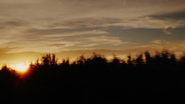 Nádherný západ slunce v přírodě a hory v pozadí. Pohled z okna autobusu