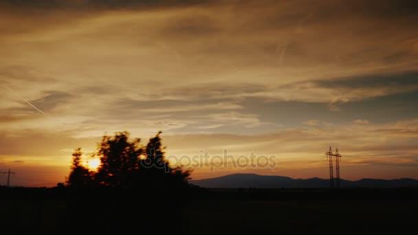 Malebná krajina, siluety stromů a hory v dálce. Pohled z okna cestování vlakem