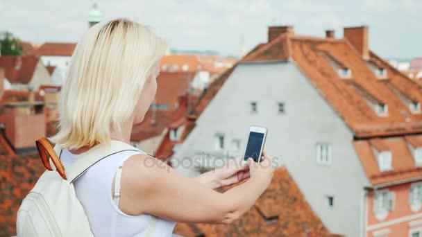 Frau Tourist macht Fotos von der Altstadt der schönen Stadt Graz. Sind Sie auf dem Bild sichtbaren roten Ziegeldächer der Stadt und der alten Häuser. Tourismus in Europa