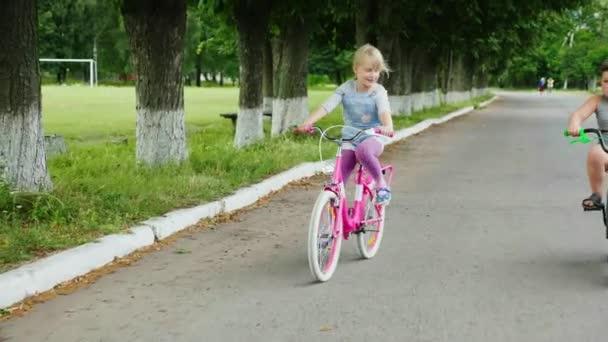 Dvě šťastné děti - holku a kluka na ulici jezdí na kole. Steadicam shot
